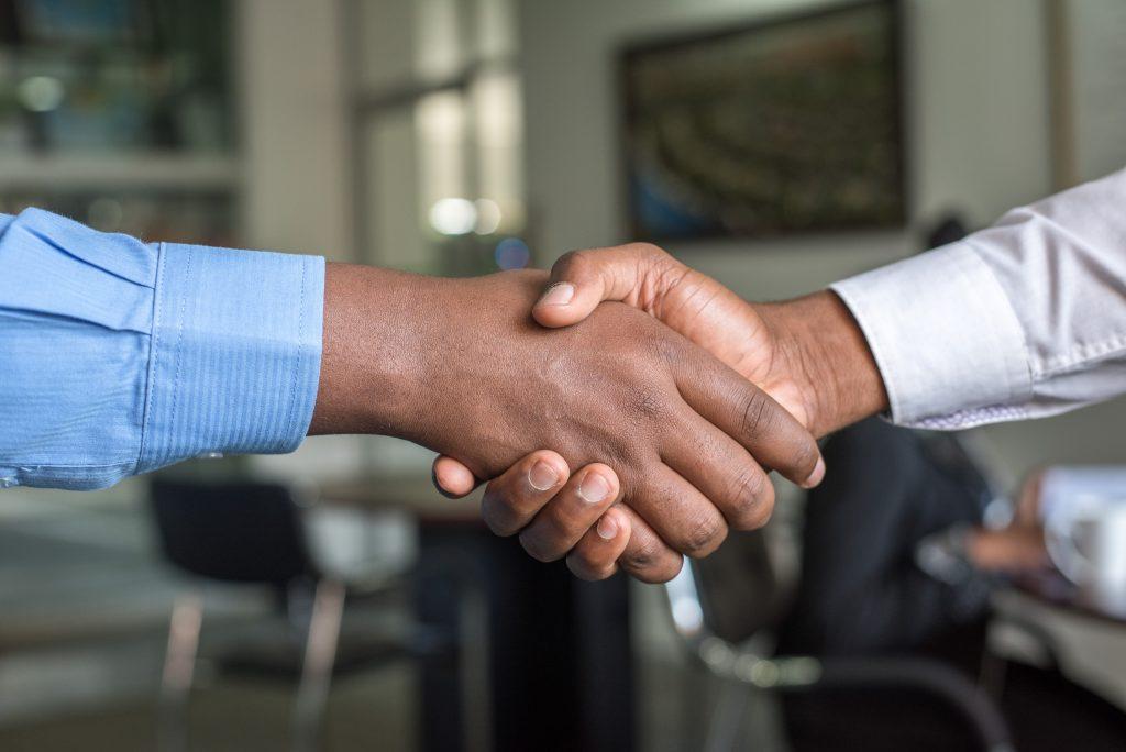 Em primeiro plano dois homens com roupa social apertando as mãos. Ao fundo um escritório.