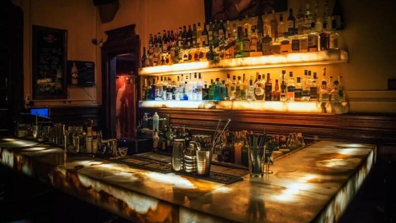 Balcão de bar, prateleiras com garrafas de bebida