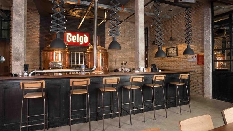 Balcão de bar industrial, seis banquetas de madeira, luminárias pendentes, parede de tijolos