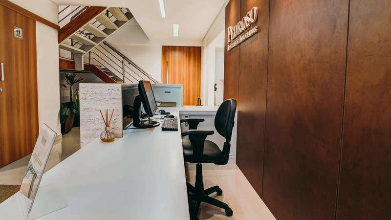 Bancada de recepção com computador e cadeira de escritório