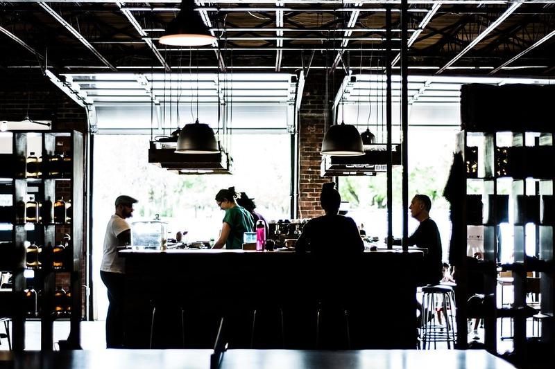 Bar bem iluminado com clientes ao redor de balcão