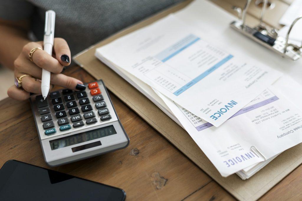 Mão utilizando calculadora sobre mesa ao lado de várias contas de papel