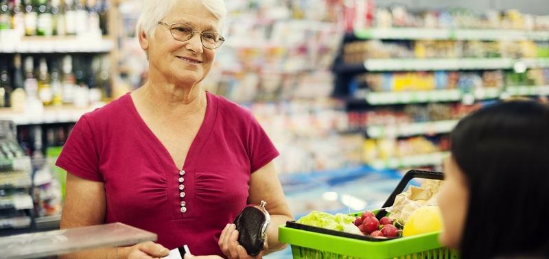 Senhora de idade passando compras em caixa de supermercado