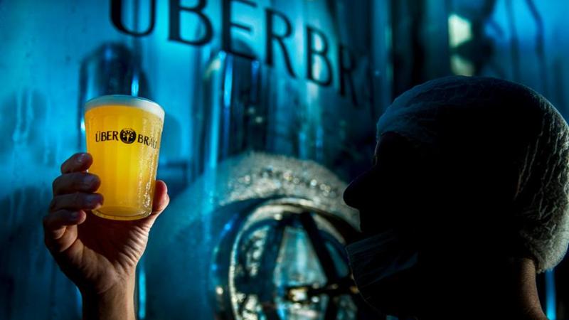 Técnico de produção observando um copo de cerveja Uberbrau em cervejaria.