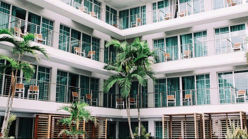 """Hotel de quatro andares em forma de """"V"""". Quartos com cortinas verde-água e cadeiras do lado de fora. Coqueiros no térreo."""