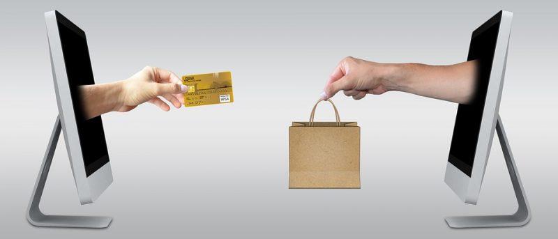 Um monitor de computador de frente para outro. De dentro saem duas mãos: uma com cartão e outra com sacola de compras.
