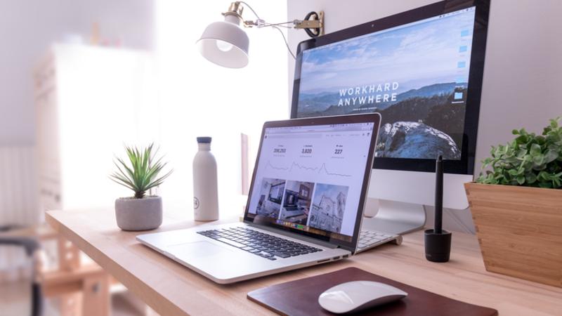 Escrivaninha com um notebook aberto, um monitor, mouse, vaso de plantas e luminária