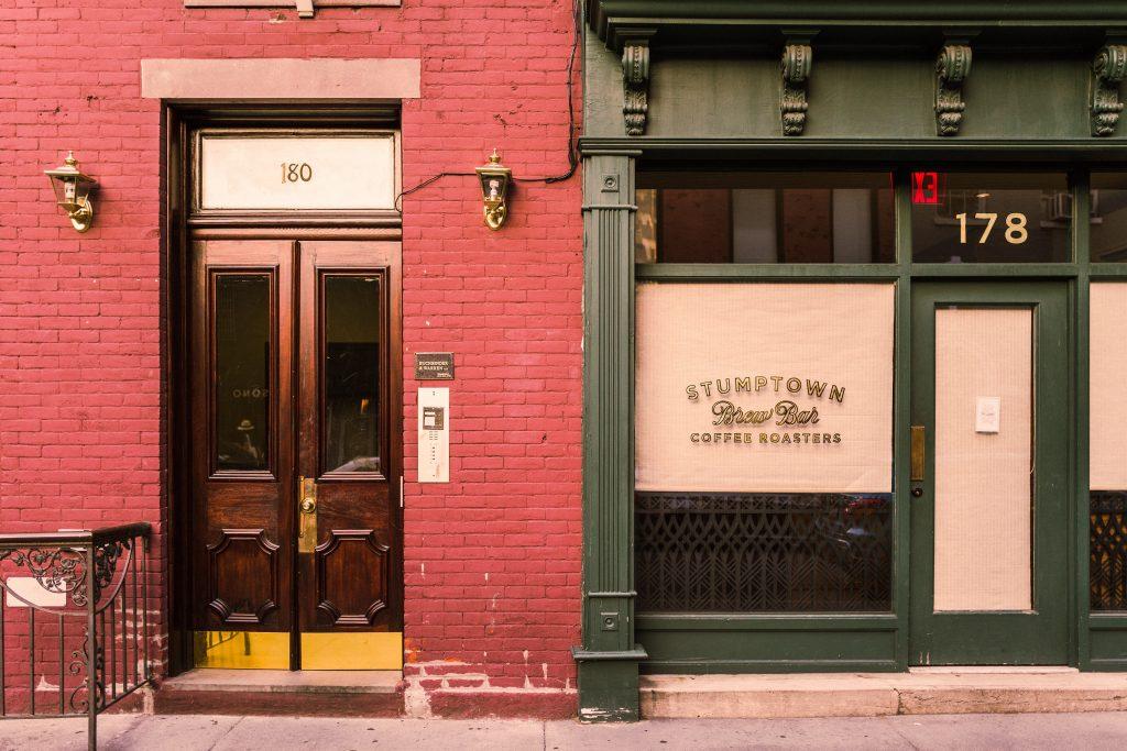 Fachada de duas lojas, uma com parede de azulejos pintada de vermelho, outra verde escuro