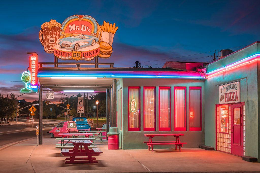 Fachada de restaurante fast food, luzes neon, placa com hambúrguer e batata frita