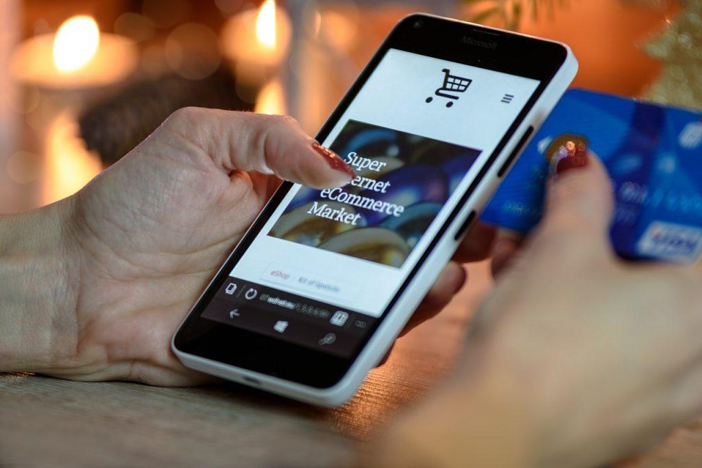 Mão segurando celular e outra segurando cartão de crédito para compra online