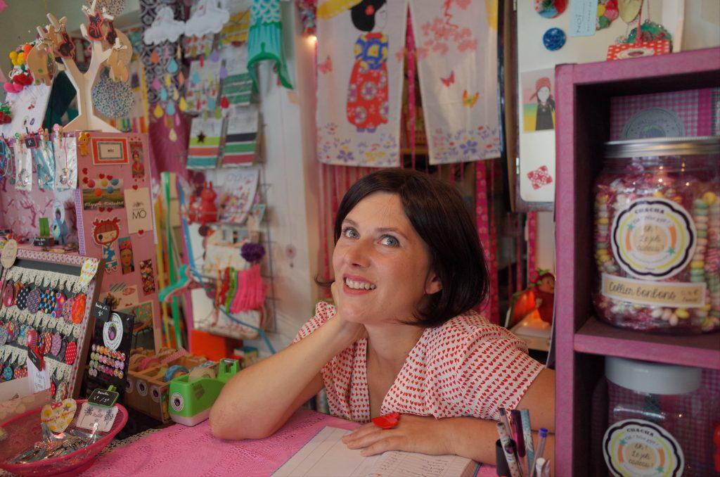 Mulher de cabelos curtos atrás do balcão de loja com vários produtos infantis, doces e decoração cor-de-rosa