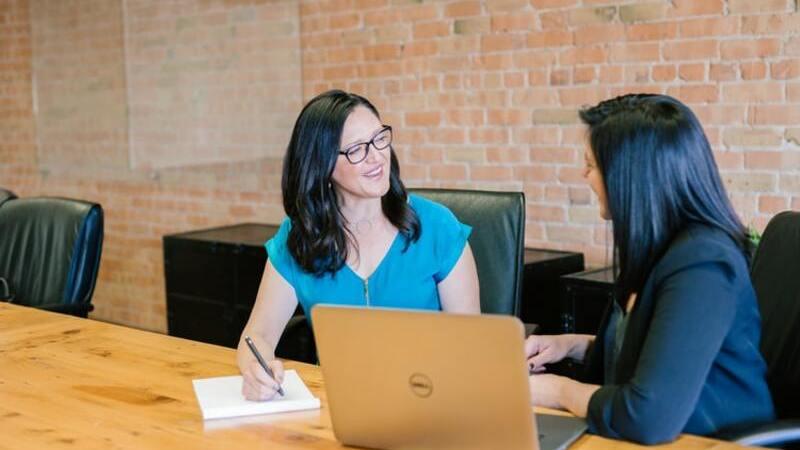 Duas mulheres sentadas conversando em mesa no escritório, um notebook à frente
