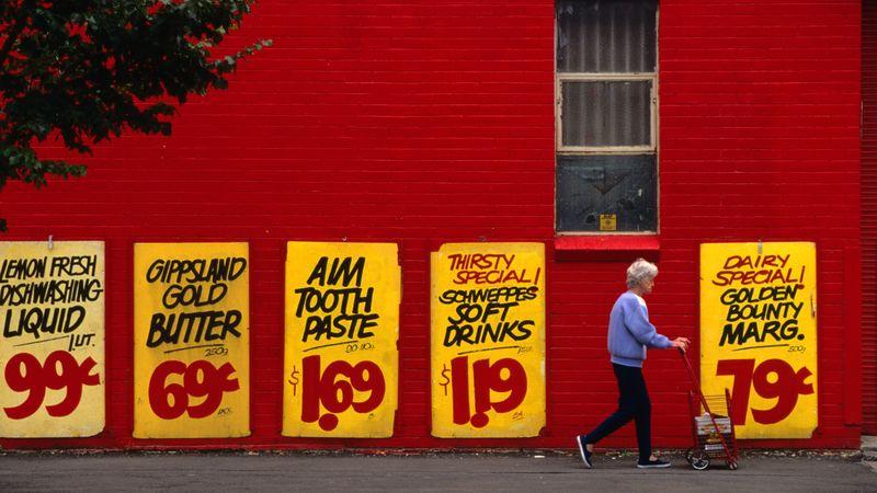 Parede vermelha com cartazes de promoção amarelos, senhora andando com carrinho de compras