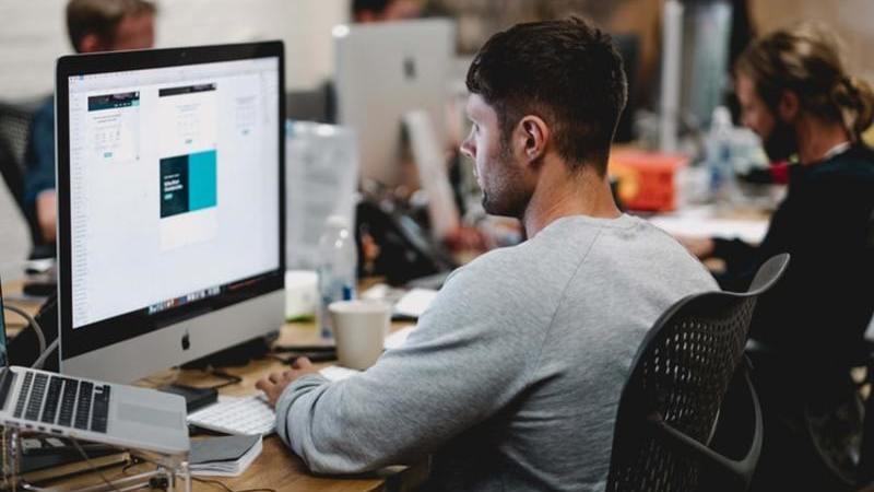 Homem sentado na mesa de trabalho olhando para monitor grande e notebook do lado