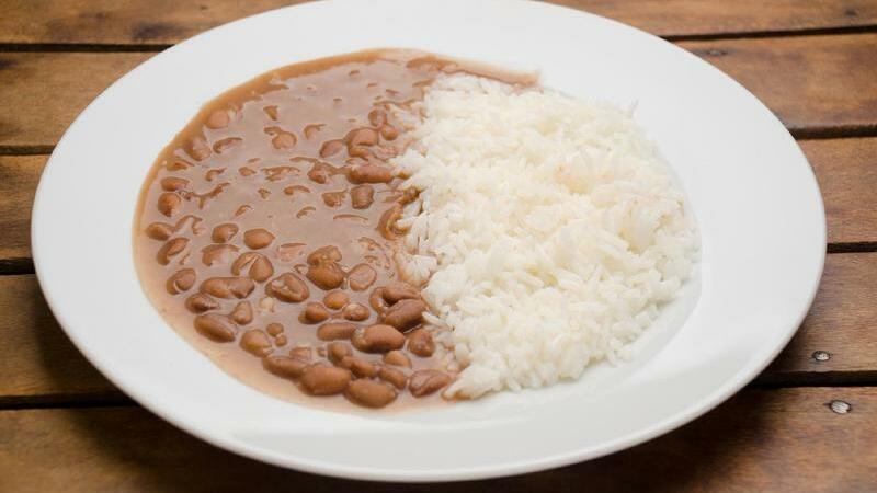 Prato de arroz e feijão sobre mesa de madeira
