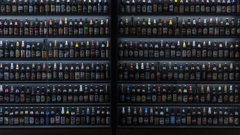 Refrigerador com seis prateleiras cheias de garrafas diferentes de cerveja artesanal
