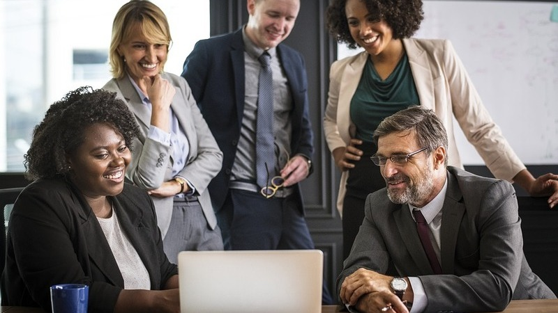 Três mulheres e dois homens olhando para a tela do notebook e sorrindo, reunião de negócios