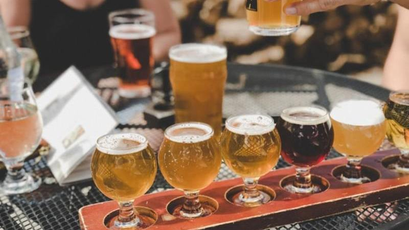 Bandeja com cinco taças de cerveja artesanal diferentes em mesa de bar