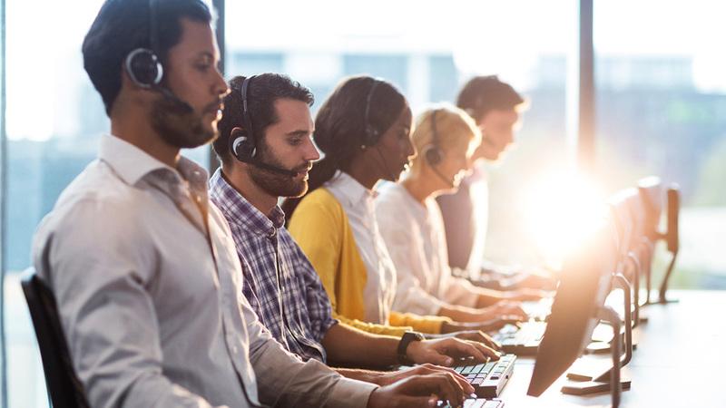Cinco pessoas em uma bancada de frente para computadores usando fone de ouvido com microfone