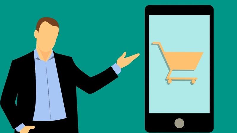 Vetor que mostra homem de terno apontando para um smartphone com carrinho de compras na tela