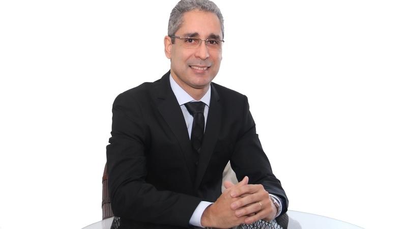 Artur Ximenes, palestrante de vendas, sentado em mesa