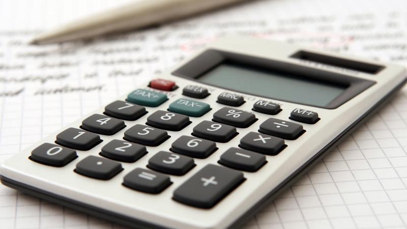 Calculadora sobre mesa com papel e caneta