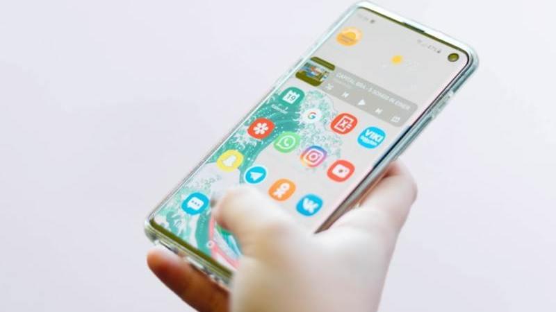 Mão segurando smartphone prateado