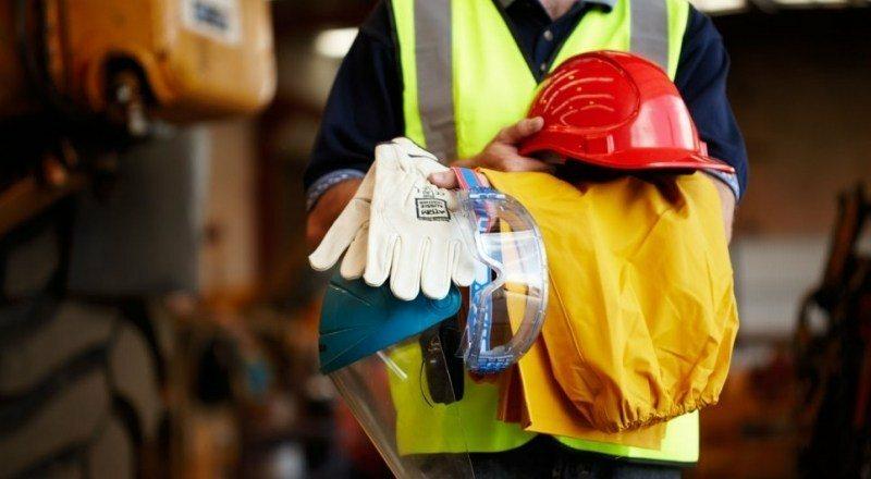 Pessoa segurando equipamentos de segurança para construção