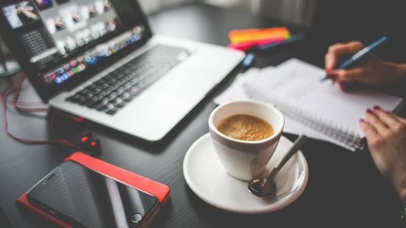 Mesa de trabalho com notebook aberto, xícara de café, smartphone e pessoa fazendo anotações em caderno