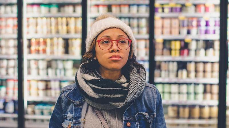 mulher à frente da prateleira de bebidas no supermercado