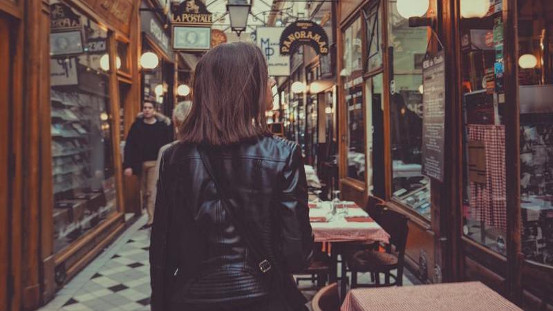 Mulher de costas caminhando por um corredor de lojas