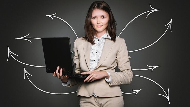 Mulher executiva segurando notebook, ilustração de várias setas saindo da figura de uma mulher executiva