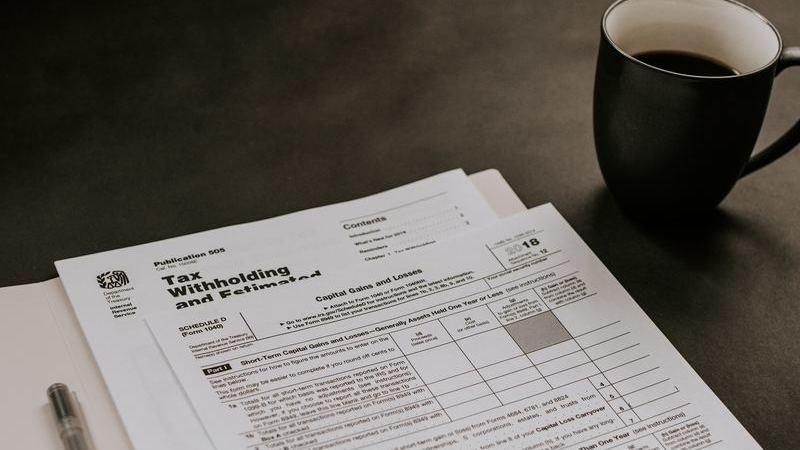 Folhas de papel sobre mesa ao lado de caneta preta e caneca preta com café