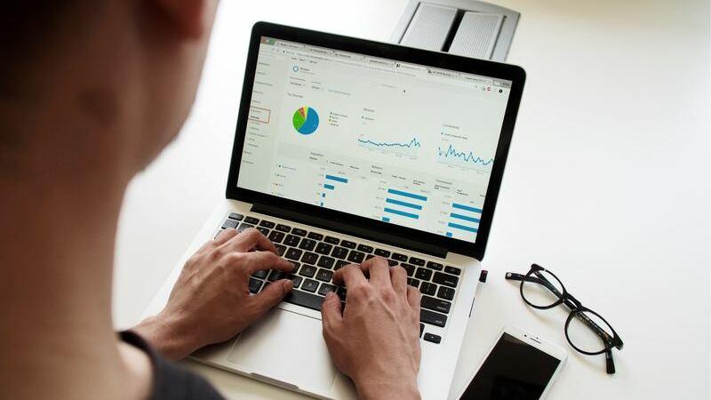 pessoa analisando gráfico, mesa com óculos e smartphone