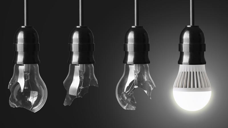 Fileira de lâmpadas incandescentes quebradas com uma LED acesa.