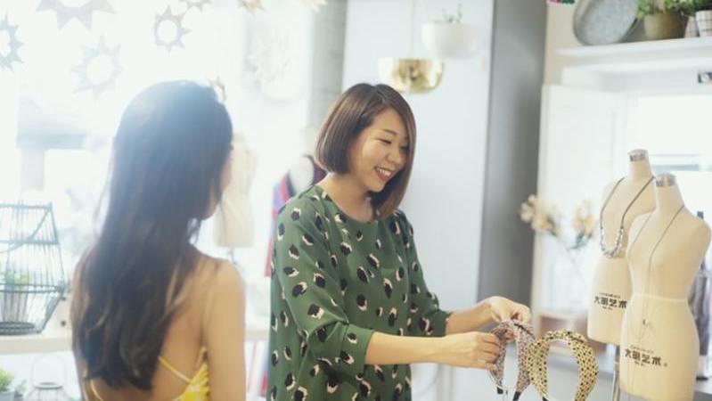 Mulher de costas conversa com mulher de blusa verde segurando tiara amarela