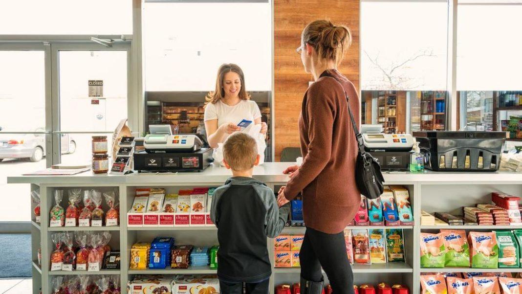 Mulher segurando criança pela mão no checkout da loja, balcão de checkout com produtos variados nas prateleiras e atendente do outro lado