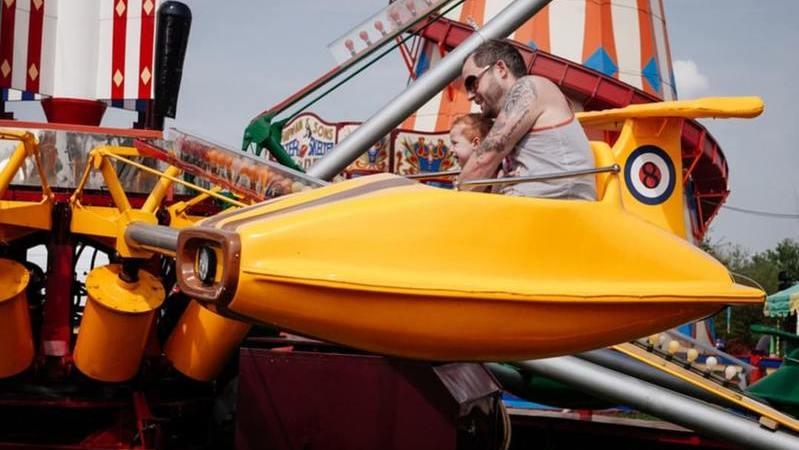 Homem e criança em brinquedo no parque de diversões