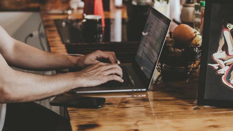 mão digitando no notebook, com smartphone ao lado, sob a mesa de madeira.