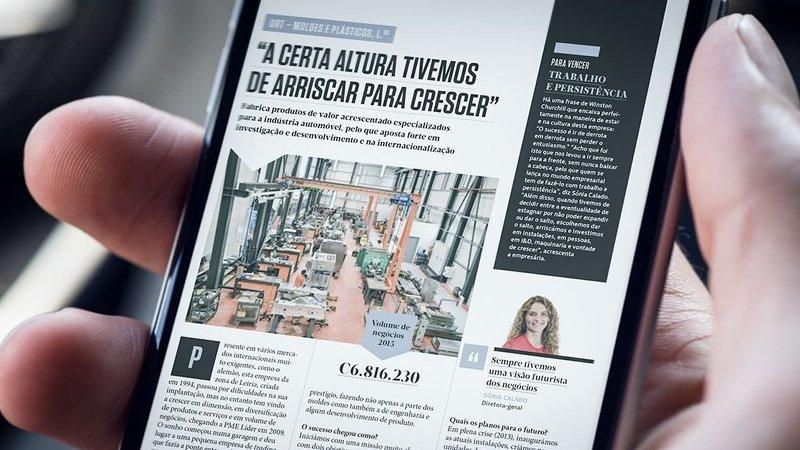 Mão segurando smartphone mostrando versão digital da revista Exame PME