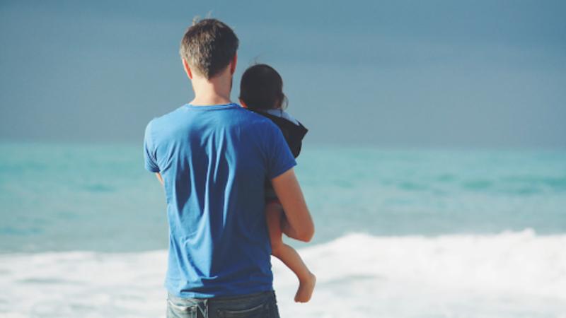 Homem de costas de frente para o mar segurando um bebê no colo