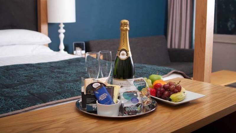 Bandeja na mesa do quarto de hotel com garrafa de champanhe, duas taças, doces, frutas e petiscos