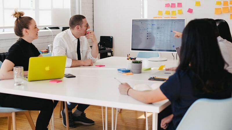 Reunião com gestor de recursos humanos em sala com monitor e post-its na parede