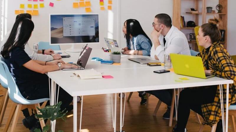 Pessoas sentadas em uma mesa de escritório olhando para uma tela