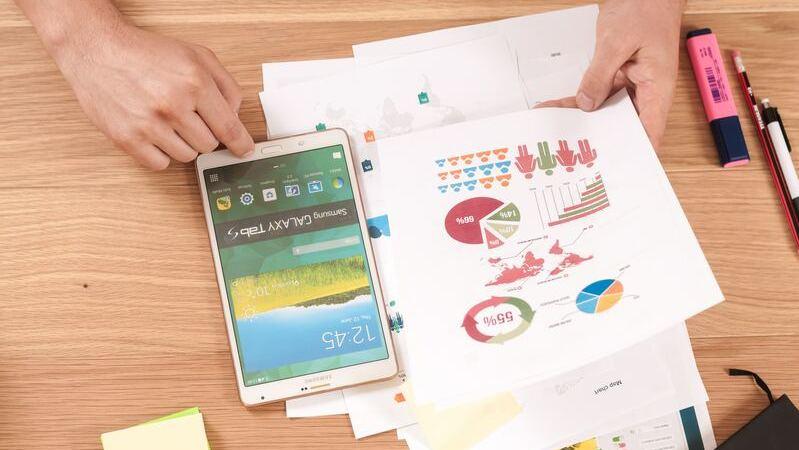 Pessoa manuseando smartphone e uma folha de papel com estatísticas
