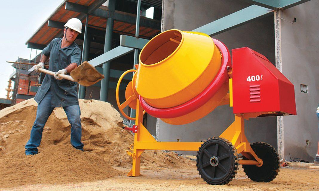 Trabalhador em obra colocando areia em betoneira