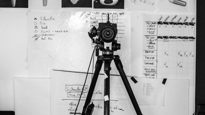 Câmera montada em tripé à frente de quadro com fotos de produtos.