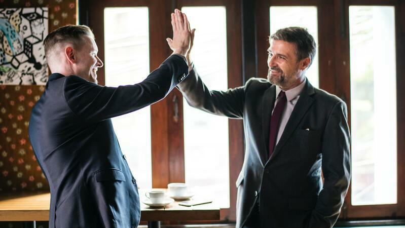 Dois homens de terno fazendo gesto de vitória
