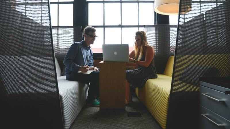 Homem e mulher olhando para computador em reservado com 2 sofás.
