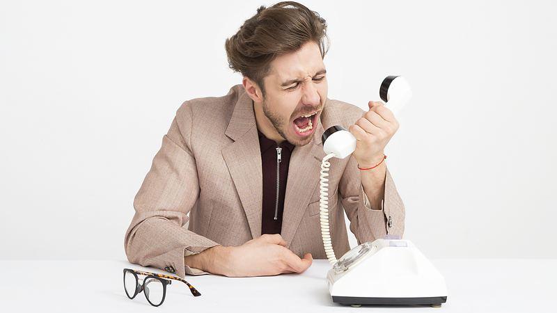Homem gritando em telefone branco